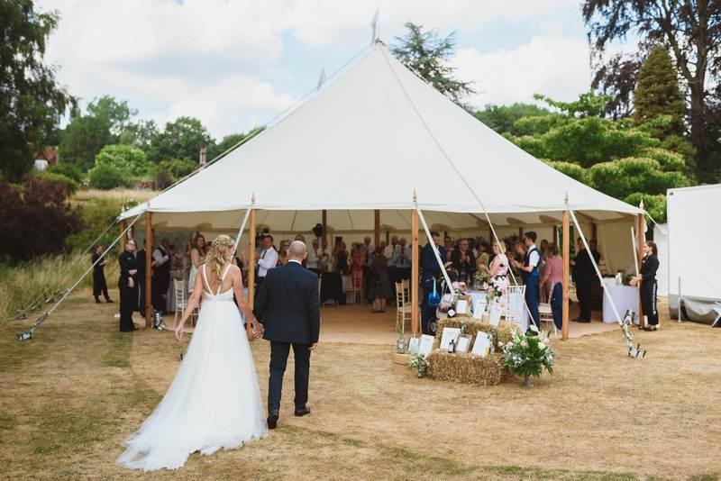 Bride and groom entering wedding tent